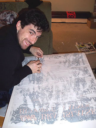 Golub hard at work, peeling off layers of excess paper from the back of a rare poster.